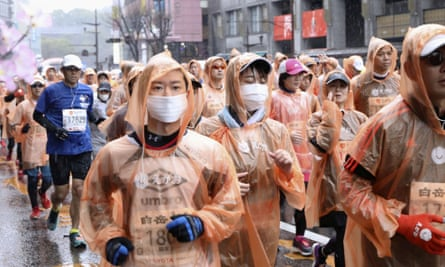Runners, some wearing masks, compete on Sunday in a marathon in Kumamoto city, western Japan.