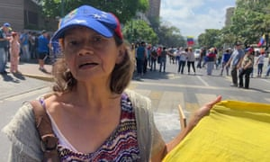 Cecilia Fernández, on the streets of Caracas, surrounded by other demonstrators carrying Venezuelan flags