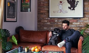 Dominic Cooper on a brown leather sofa with his pet dog, a bare brick wall with a painting on it behind, a bowl of fruit on a table in front
