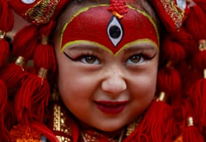 A girl dressed as the living goddess Kumari participates in Kumari Puja