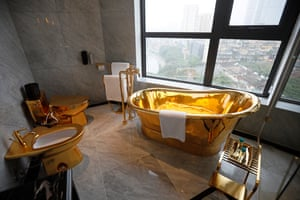 A gold-plated bathtub and toilet with a view