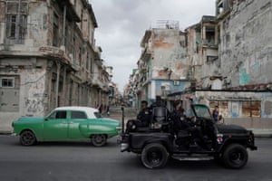 A special forces vehicle passes a vintage car in downtown Havana
