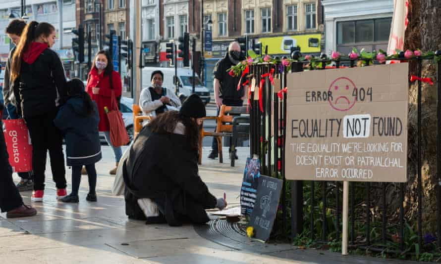 A woman writes a note at a public memorial site in Brixton, south London, to draw attention to the increase in domestic and workplace violence against women and non-binary people during the pandemic.