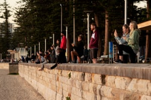 People watch the sunrise at Manly beach.
