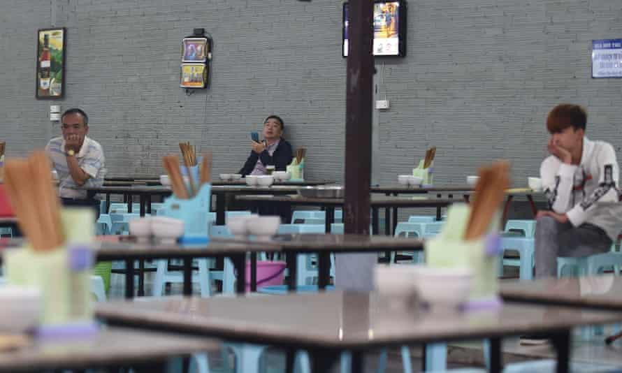 A lone drinker has a beer while waiters wait for customers at a bar in Hanoi.