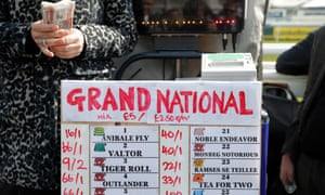 A bookmaker counts her money before the Grand National on Saturday.