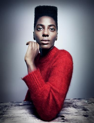 Ysra Daley-Ward  in a red jumper looking directly at the camera, her elbow on a table in front of her