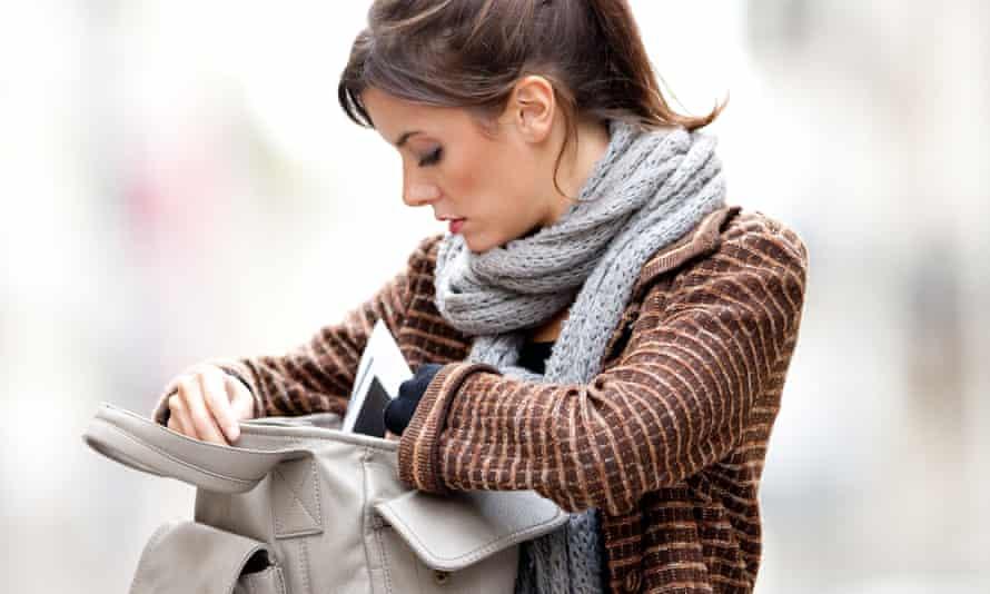 A woman searches her handbag.