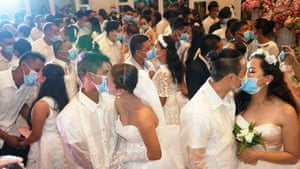 Bacolod City, Philippines: Filipino couples kiss while wearing their face masks in a government-sponsored mass wedding