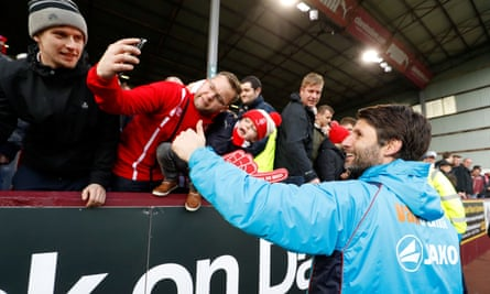 The Lincoln City manager, Danny Cowley, celebrates with fans after his team's historic FA Cup victory over Burnley at Turf Moor.
