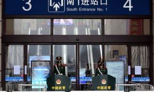 Chinese paramilitary officers wearing masks stand guard at an entrance of the closed Hankou Railway Station after the city was locked down following the outbreak of a new coronavirus in Wuhan.