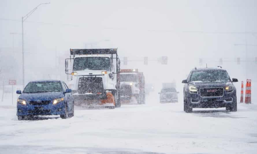 Cars and plows are driven during a winter storm on Sunday in Oklahoma City.