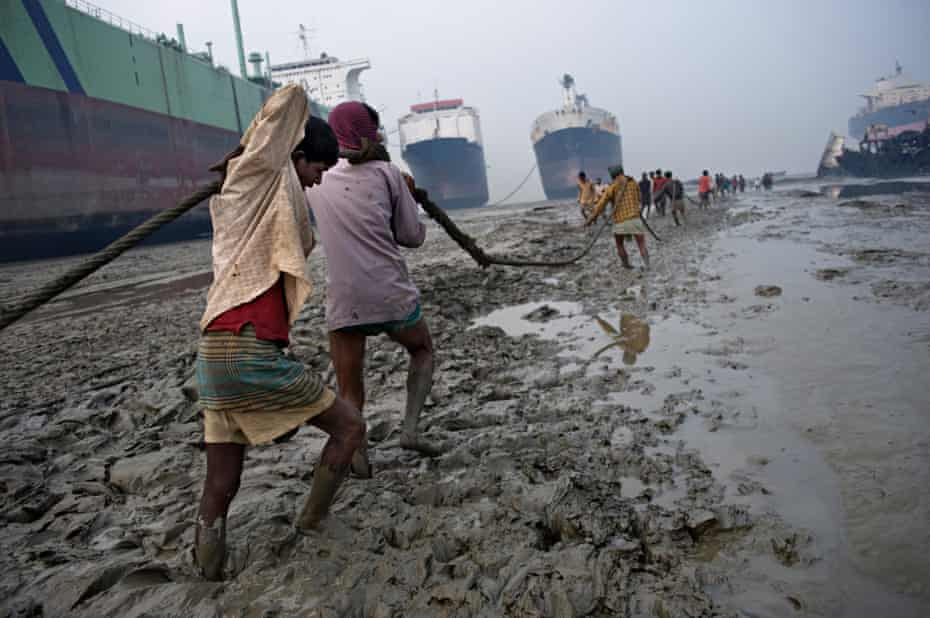 Labourers pull rope on the muddy beach of Chittagong, with huge tankers in the background.