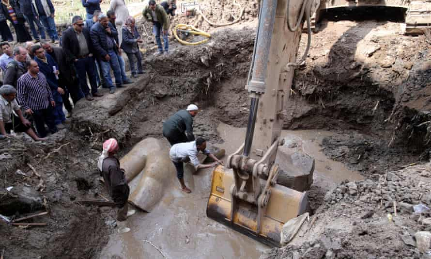 A mechanical digger is employed to clear mud away and allow access to the statue.