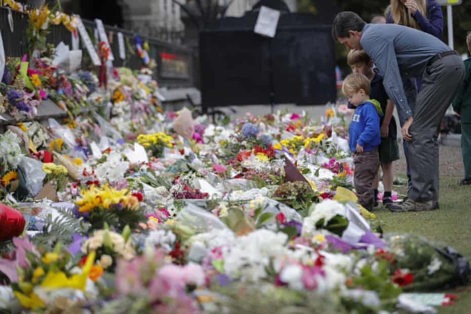 Mourners lay flowers on a wall at the Botanical Gardens in Christchurch, New Zealand, after the shootings.