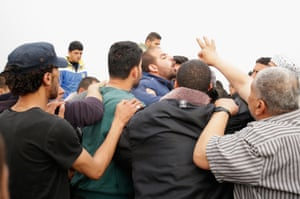 An auctioneer crowded by buyers at the Gaza sea port