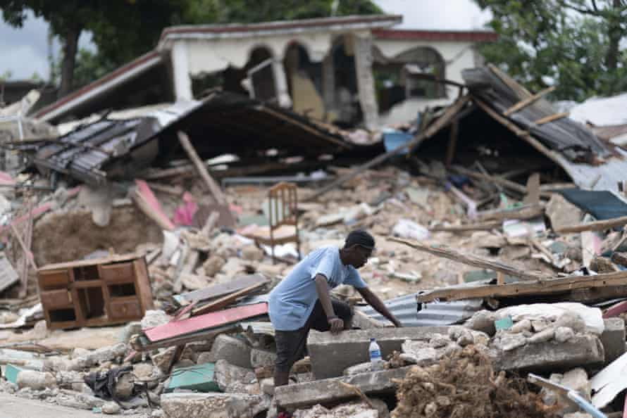 A man searches in the debris of a collapsed house after an earthquake, in Les Cayes, Haiti, on 16 August 2021.