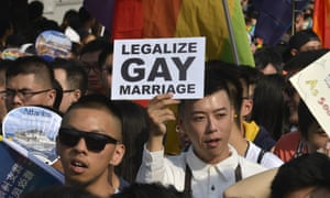 A supporter of same-sex rights holds a sign during the Taipei gay pride parade