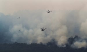 Helicopters drop water on a bushfire near Yinnar in Gippsland, Victoria