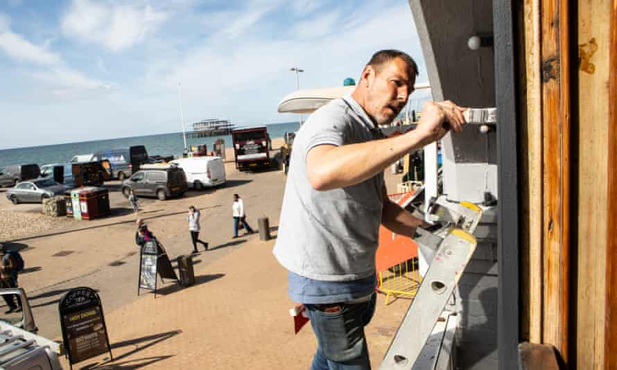 Painter Dale Black works on the exterior of the Copper Clam restaurant on Brighton's seafront