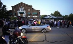 A large crowd of protesters gather outside the house, right, where Atatiana Jefferson was shot Saturday and killed by police, during a community vigil for Jefferson on Sunday, in Fort Worth.