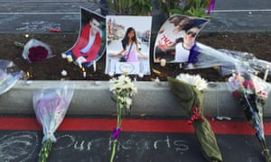 Photos of Jordan Ebner, Anna Bui and Jake Long are seen at a makeshift memorial as people gather in the parking lot of Kamiak High School in Mukilteo, Washington.