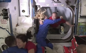 Soichi Noguchi is greeted by Kate Rubins as he enters the International Space Station