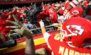 Tyreek Hill celebrates after scoring a touchdown by jumping into the stands and manning a television camera
