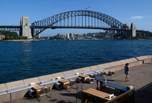 A lone woman walks through a quiet Opera Bar in front of the Sydney Harbour Bridge, Sydney, Saturday, March 21, 2020.