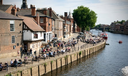 People drink in the bars on the banks of the River Ouse in York town centre in North Yorkshire.