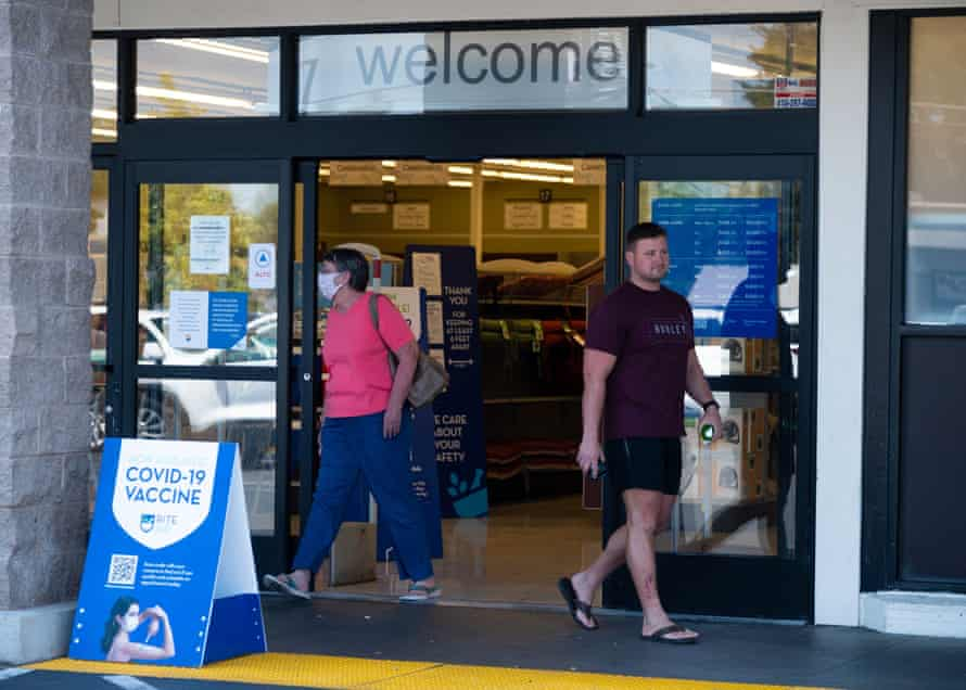 A woman wearing a mask and a man not wearing a mask exit a Rite Aid drug store in Sacramento.