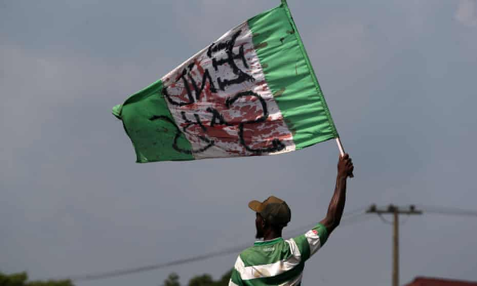 A protester holds a stained Nigerian flag