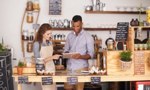 coffee shop owner showing a waitress the ropes