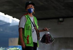 Street vendor Antonia Pudjiastuti offers cloth face masks for sale under a bridge in Jakarta, Indonesia
