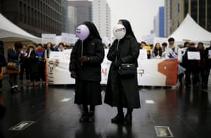 Nuns hold balloons before the start of a rally in Seoul, South Korea