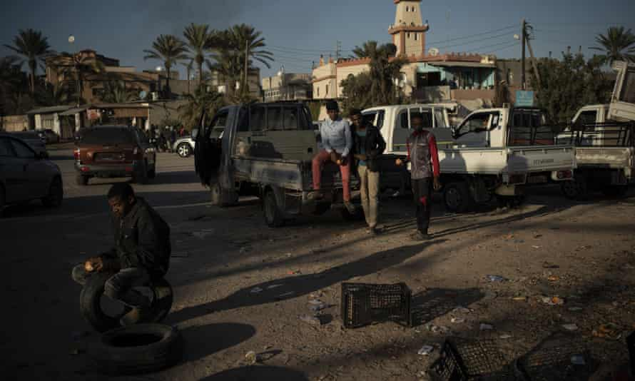 People from Niger looking for jobs wait at a crossroads in the outskirts of Tripoli, Libya.