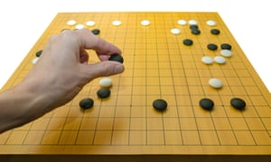 A hand placing a stone on a go board.