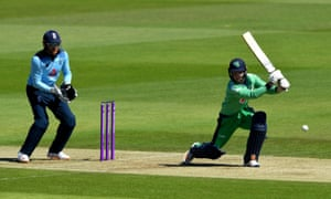 Ireland's Curtis Campher bats as England wicketkeeper Jonny Bairstow looks on.