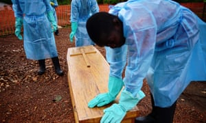 Sierra Leonese government burial team members wearing protective clothing stand next to a coffin