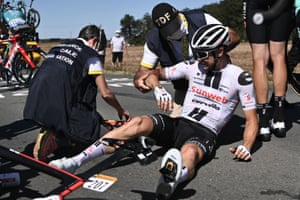 Team Sunweb rider Nicolas Roche is helped by medics after crashing.