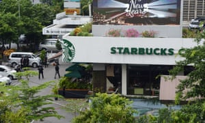Police secure the area outside a Starbucks coffee shop after a series of explosions in central Jakarta