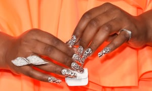 A close-up of Lizzo's hands, against her orange dress, holding a tiny white handbag between her fingers, her long nails painted with silver glittery varnish