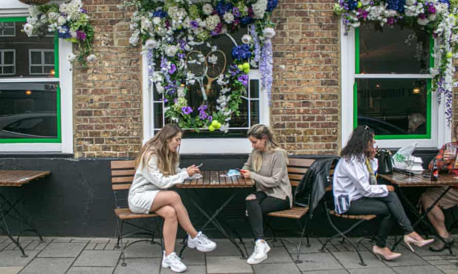 People sit outside a pub in Wimbledon village decorated with a tennis theme for the championships.