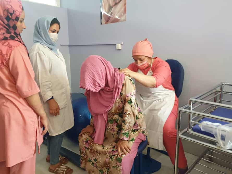 A woman is supported in active labour by three midwives.