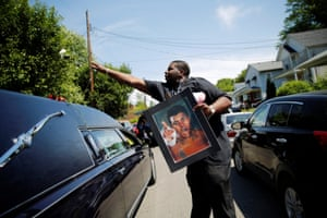 A man throws a rose over the hearse carrying the remains of Muhammad Ali