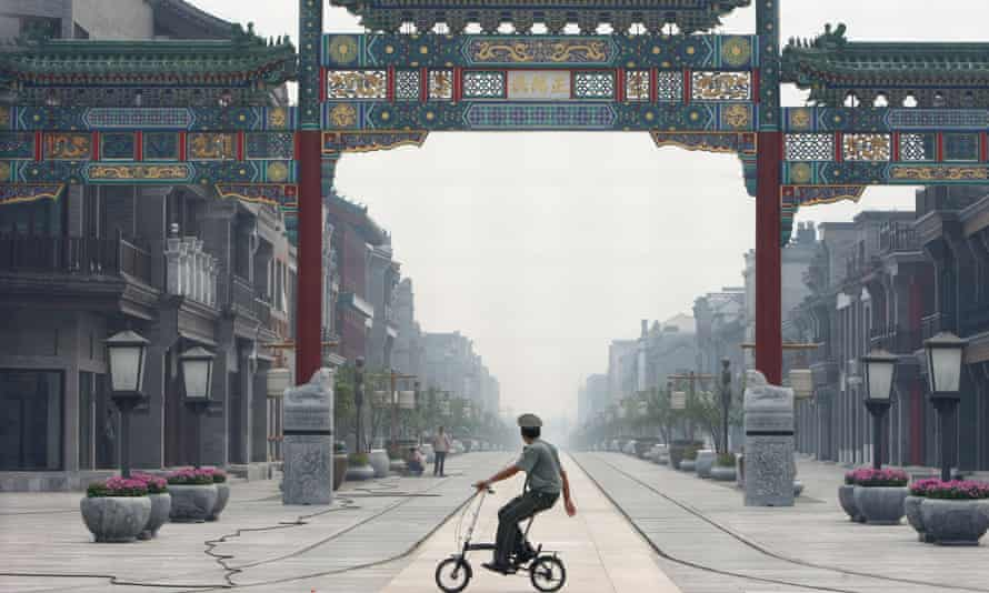 A security guard rides a bike at the Qianmen Avenue, a traditional commercial street in Beijing, China.