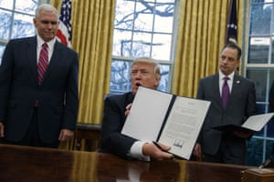 Mike Pence and Reice Priebus look on as Donald Trump shows off an executive order to withdraw the US from the 12-nation Trans-Pacific Partnership trade pact.