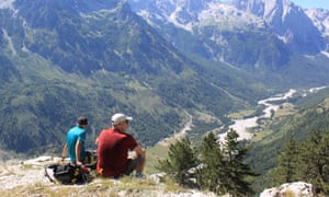 View finder: hikers look out over Valbona, a beautiful valley with distant mountain peaks.