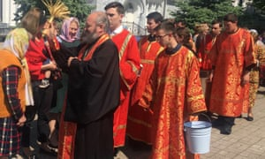 Clergy flick holy water over the faithful at Tashkent's Cathedral of the Assumption