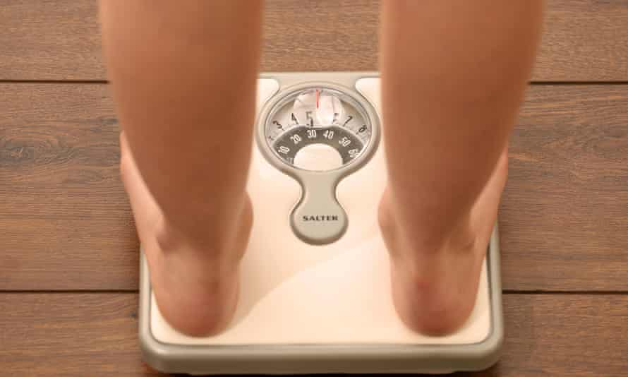 A person weighs themself on some bathroom scales